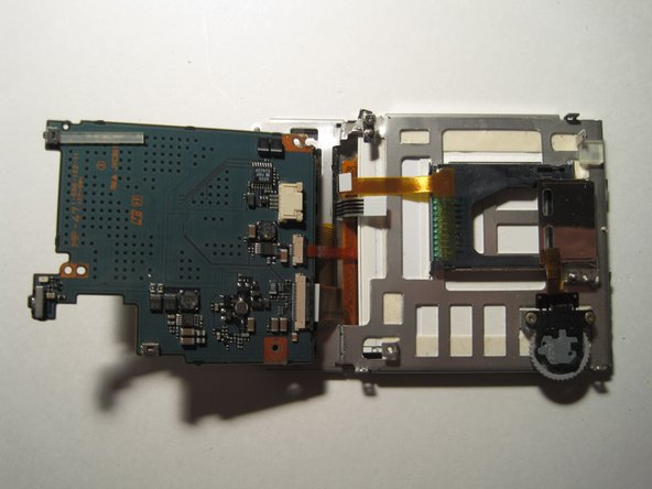 Next, flip the board over so you can see the back side.  There should be 3 ribbons attached to the circuit board.  (In the picture the white one was not attached as it easily came out when I flipped the board over.)  Remove these ribbons from their connectors by simply pulling them out.  The circuit board should fully separate from the frame holding the screen now.