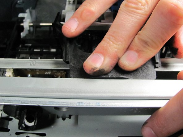 For proper reassembly, place the printer carriage's black lip beneath the overhanging metal flap at the back of the printer.