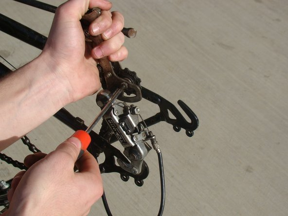 Rotate the derailleur arm forward to access the phillips head screw from the forwardmost sprocket. Remove the screw.