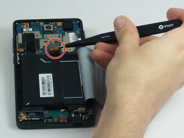 Image 2/3: Proceed to gently remove the tape like connector from the battery until it is completely off.