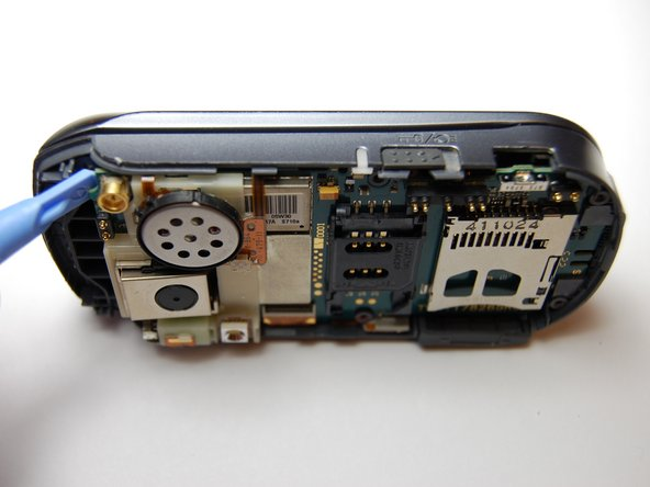 Use the plastic prying tool to loosen the motherboard from the phone.