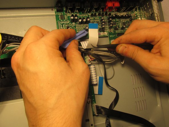Using the tweezers and the blue plastic opening tool, disconnect the ribbon cables from the green circuit board where the I/O ports are attach to.