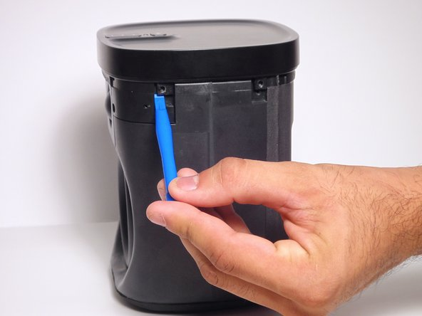 Using a plastic opening tool, pry open the top cap containing the power and volume button.