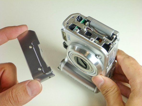 Remove the side paneling and the two remaining screws attached to the frame of the camera.