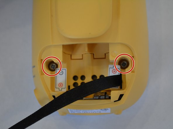 Use the Philips #00 Screwdriver to remove the two 4 mm screws located on either side of the battery slots.