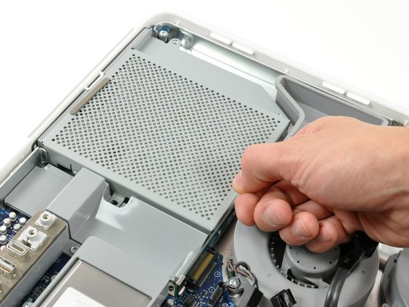 Image 1/2: Pull the optical drive up by its white pull tab to disconnect it from the logic board.