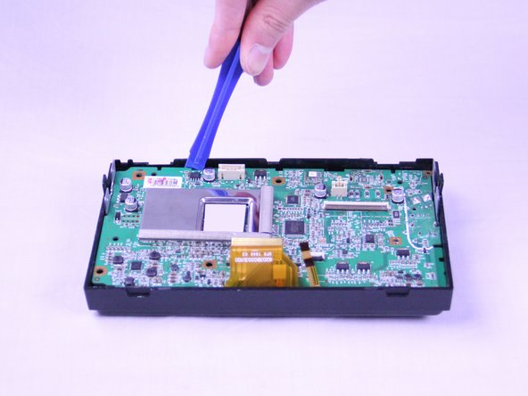 Use a plastic opening tool to remove the display board from the radio.