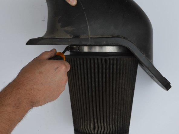 Loosen hose clamp holding air filter to air filter assembly using flathead screwdriver.