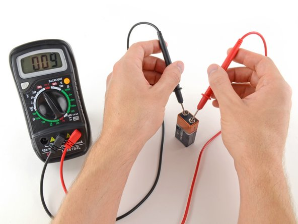 Image 1/2: If your range was set too high, you may not get a very accurate reading. Here the multimeter reads 9 volts. That's fine, but we can turn the dial to a lower range to get a better reading.