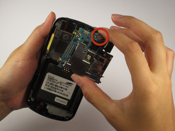 Using the prying tool, lift and remove the motherboard from the phone.