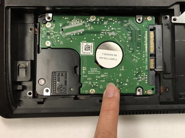 Remove the silver hard drive cover by sliding it left to reveal the green hard drive.