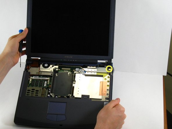 Remove the screw in the upper right corner while holding the bottom right side of the computer display.