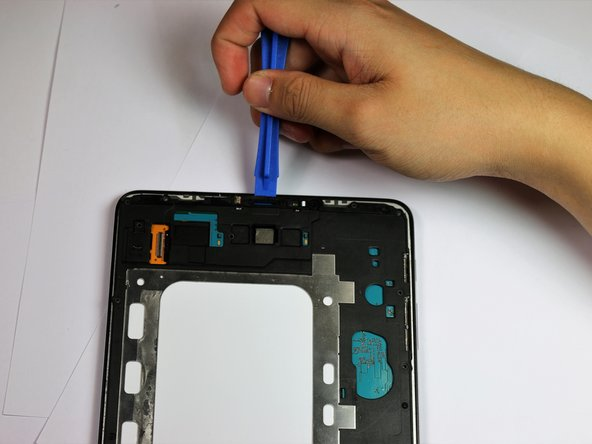 Image 2/3: Lift up and remove the panel of the board using a plastic opening tool.
