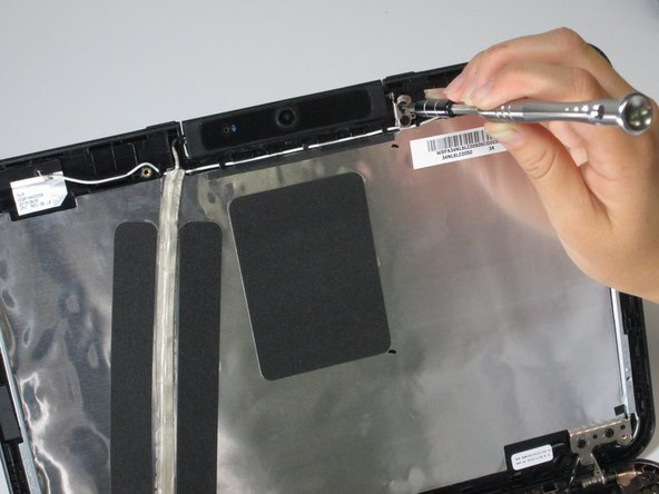 Image 1/2: Once the two screws are removed, carefully pull the camera off the top of the screen.