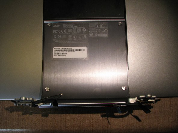 Image 2/3: Remove the 4 T9 torx screws from the display assembly where the model number and serial numbers stickers are located and swap that panel to the replacement display assembly.  Completing this step allows for your computer to retain its original identification information.