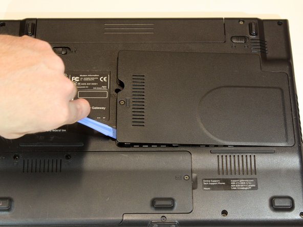 Image 3/3: Use a plastic opening tool to gently pry off the plastic cover.