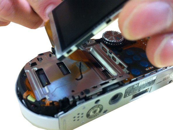 Remove the LCD screen plate by gently pulling upward on the trace until the screen is removed from the camera.