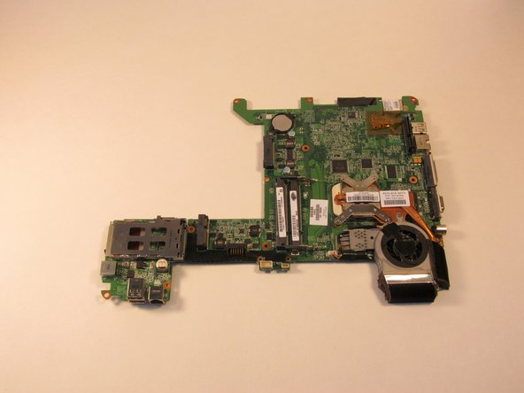 Image 2/2: Turn the system board over and lay it flat on a soft surface.
