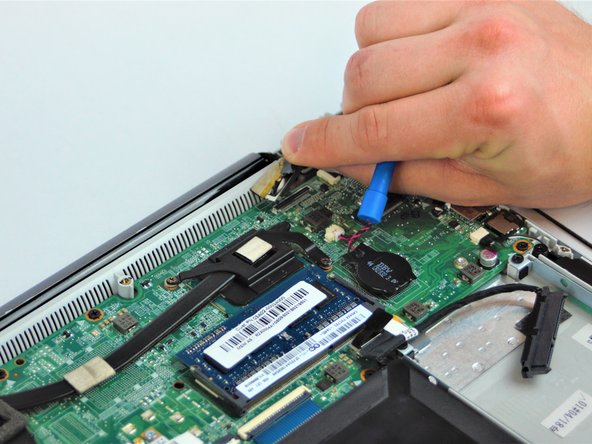 Use the plastic opening tool or spudger to lift and remove the flat top connector from the motherboard.