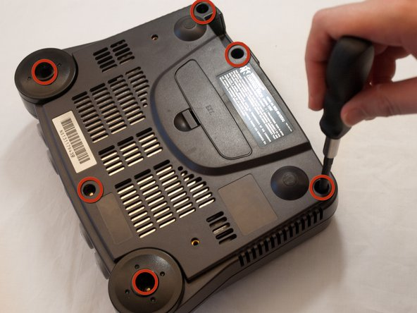 Image 1/2: Flip the console cartridge-side down and remove the six screws using a Phillips screwdriver or gamebit head.