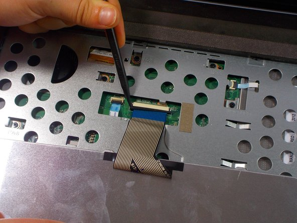 Pull each end of the black ribbon cable piece towards the mouse track pad to unlock the ribbon connector piece.
