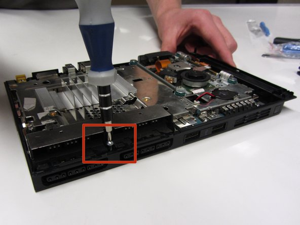 Remove the 2.4 mm screw located in between the controller ports using a #1 Phillips screwdriver.