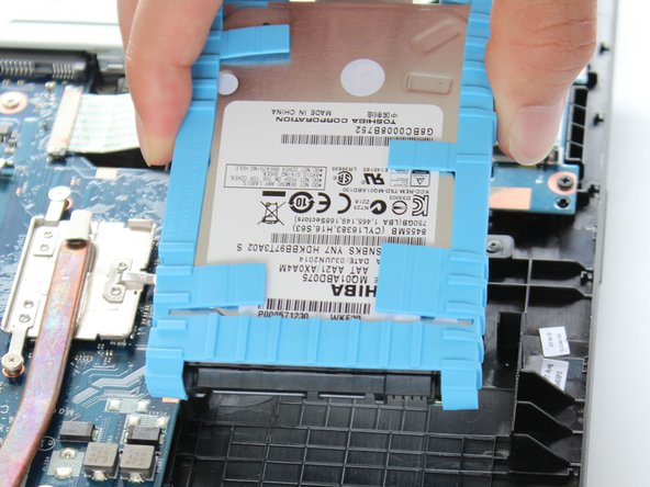 Gently lift the hard drive upward, removing it from the Toshiba device.