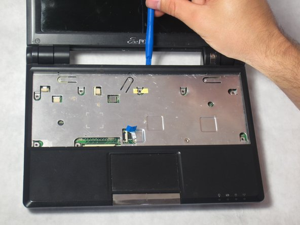 Using a plastic opening tool, remove the cover of the laptop by prying up the edges.