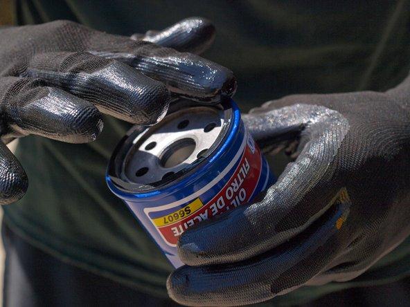 Tauche einen behandschuhten Finger in eine neue Ölflasche und verteile eine dünne Schicht Öl auf der Dichtung des neuen Ölfilters.