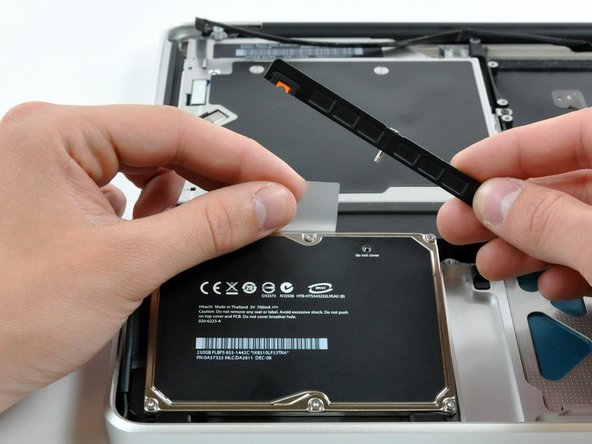 Image 1/1: Lift the hard drive by its pull tab enough to grab and remove the retaining bracket.