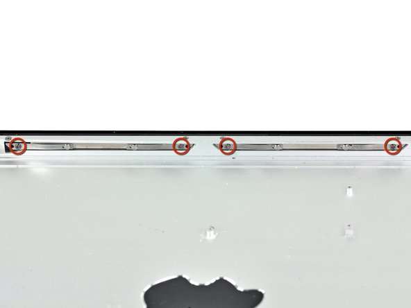 These are the magnets on the left side of the iPad 2 -- the ones that attract the Smart Cover's frame. They're integrated into the iPad 2's back cover, and held in place with four #00 Phillips screws.