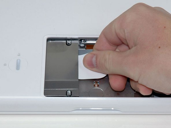 Image 1/1: Grasp the white plastic tab attached to the hard drive and pull it to the right, removing the hard drive from the computer.