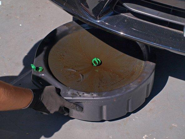 Entferne die Ölablasswanne unter dem Auto.