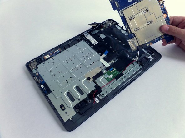 Detach the motherboard by lifting it up and away from the body of the laptop.