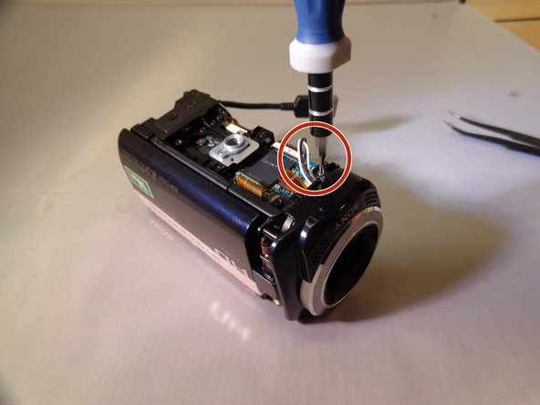 Using the PH #00 size screw driver, unscrew one 5 millimeter screw located on the top left near the lens of the camera.
