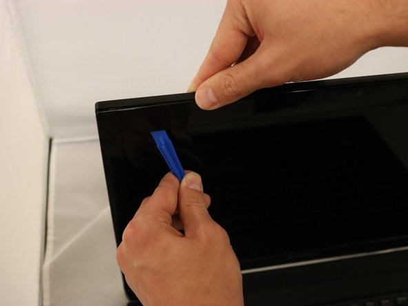 Separate the front bezel from the display panel using the plastic opening tool by gently prying around the edges and removing it.