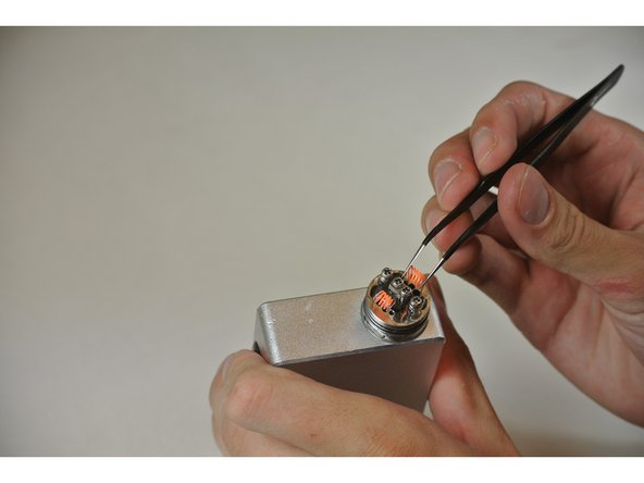 Image 1/2: '''CAUTION:''' If the tweezers are placed on the coils while the button is being pressed, the user may sustain small burns.