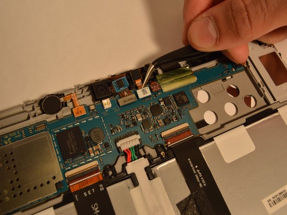 Use plastic tweezers to carefully detach the front-facing camera from the motherboard.