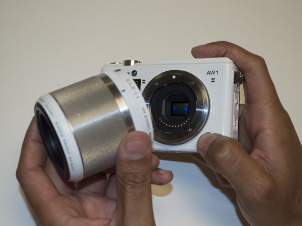 Press and hold the lens release button,  twist the lens in a clockwise motion, then pull it off of the camera.