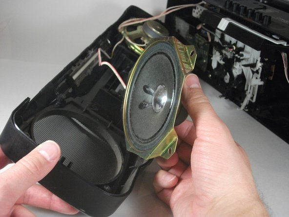 Lift the speakers out of the front face of the radio to complete the removal.