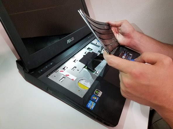 Insert a spudger, or plastic opening tool, into these five slots and pry upwards to pop up the keyboard.