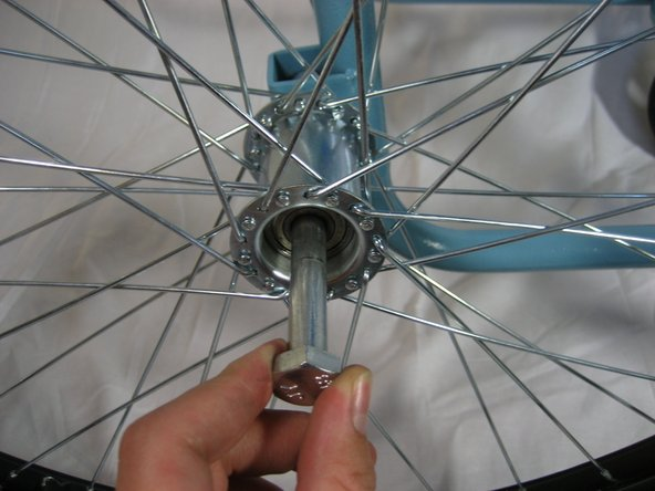 Image 3/3: Remove the axle bolt from hole and remove the wheel from the wheelchair.