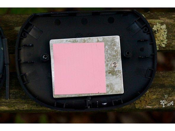 Tout d'abord, on remarque que la partie inférieure (à droite), ne contient qu'une pièce de métal et un pad thermique. Si l'on retire celui-ci, on remarque que l'appareil est sensiblement plus léger. Cette pièce, outre à servir de dissipateur thermique supplémentaire, a sûrement été choisie en vue d'alourdir l'appareil.