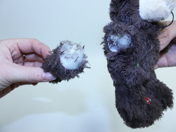 Identify the area on the stuffed animal that needs sewn back together.
