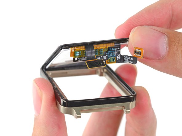 Image 2/3: A little gentle pressure from the back of the LCD gives our opening pick just the edge it needs to sneak in and separate the display from the watch bezel.