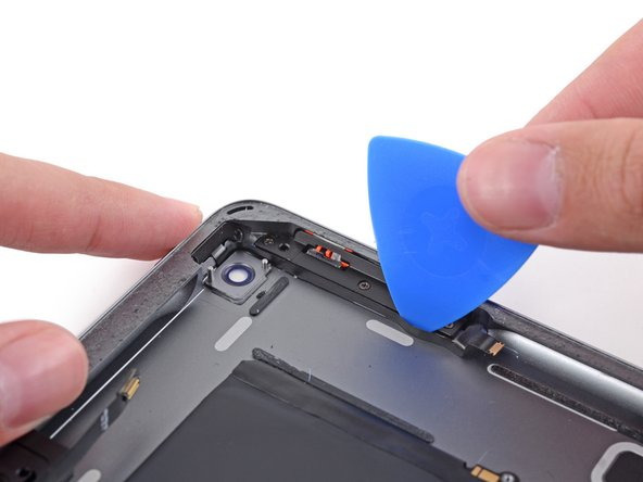 Carefully insert an opening pick between the button ribbon cable and the edge of the case.
