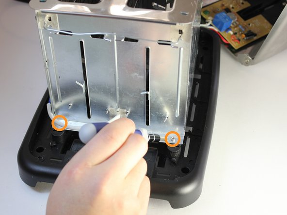 Flip the toaster around and proceed to remove the two remaining 8mm screws.