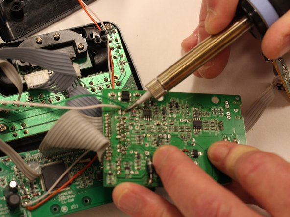 Detach speaker cables from circuit board with soldering iron