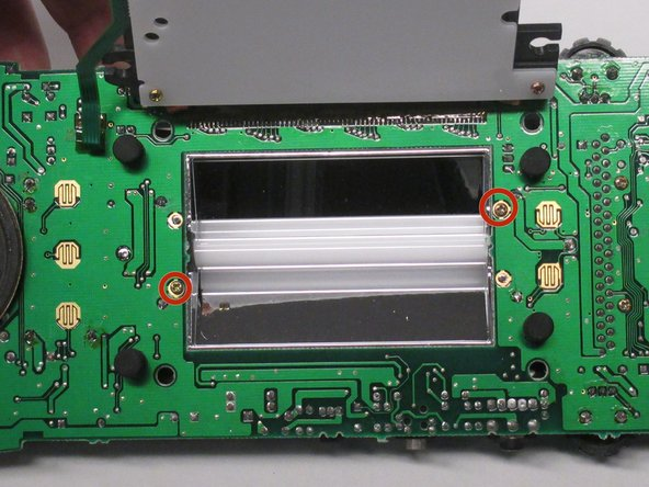 Unscrew the two 10 mm screws as shown with a Phillips #0 screwdriver in order to remove the shield behind the backlight.