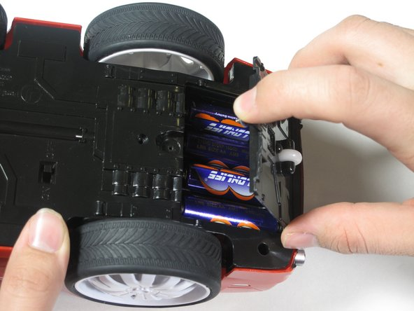 Gently lift the battery cover from the car to expose the batteries.